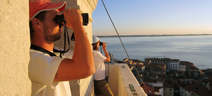 Researchers observe the sea from a historic building.